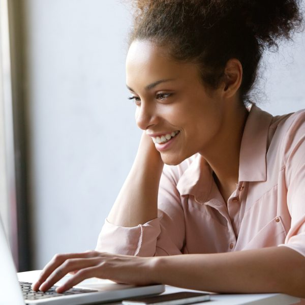 Close up portrait of a beautiful young woman smiling and looking at laptop screen